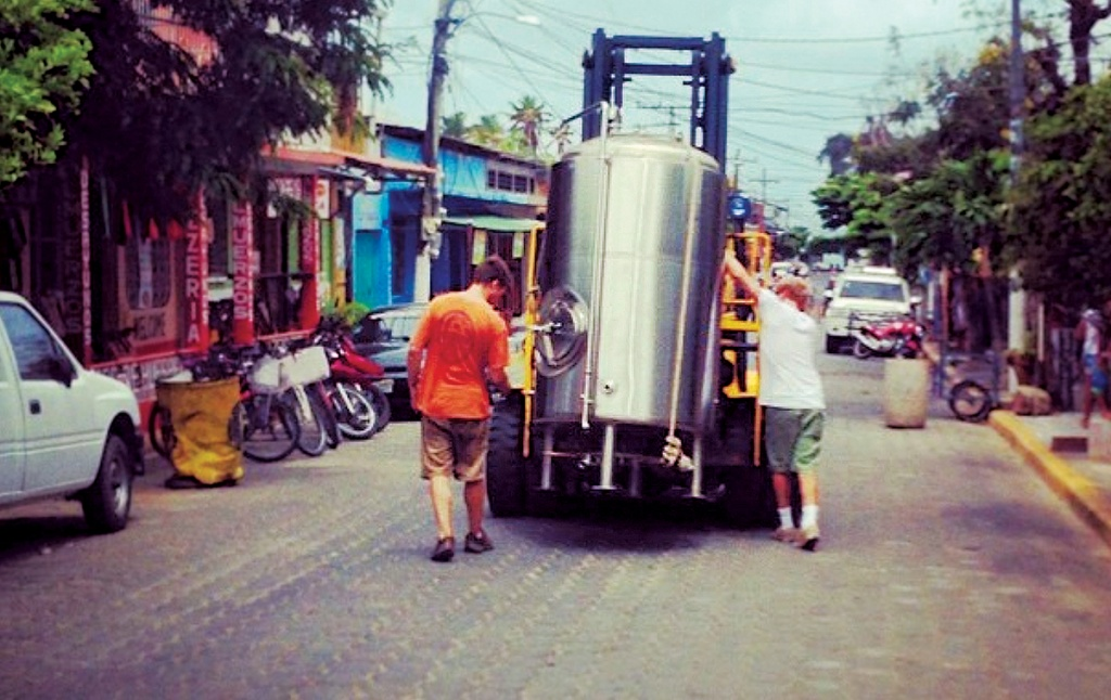 Photo of Greenberg and an associate walking with a forklift that's carrying brewing equipment through San Juan del Sur, Nicaragua.