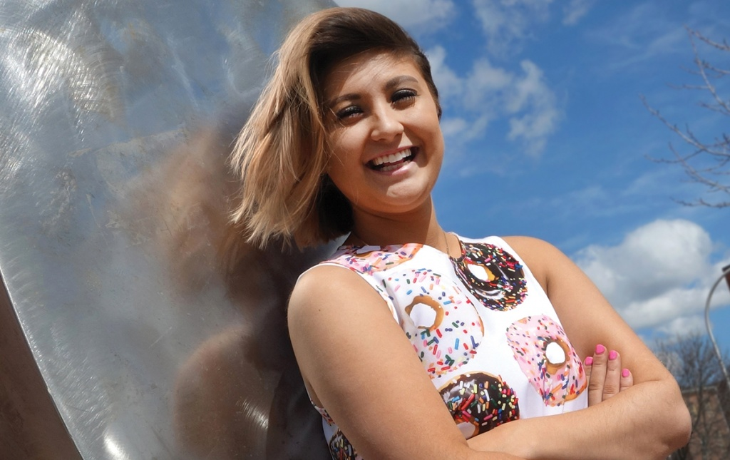 Photo of Rachael Cholak '18 wearing a dress printed with donuts, in front of a large sculpture shaped like a donut.