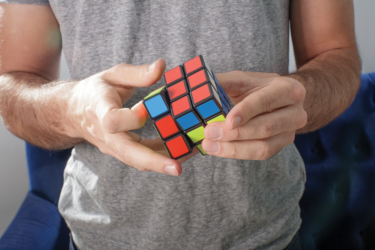 A photograph of Max Deutsch's hands playing with a Rubik's Cube.
