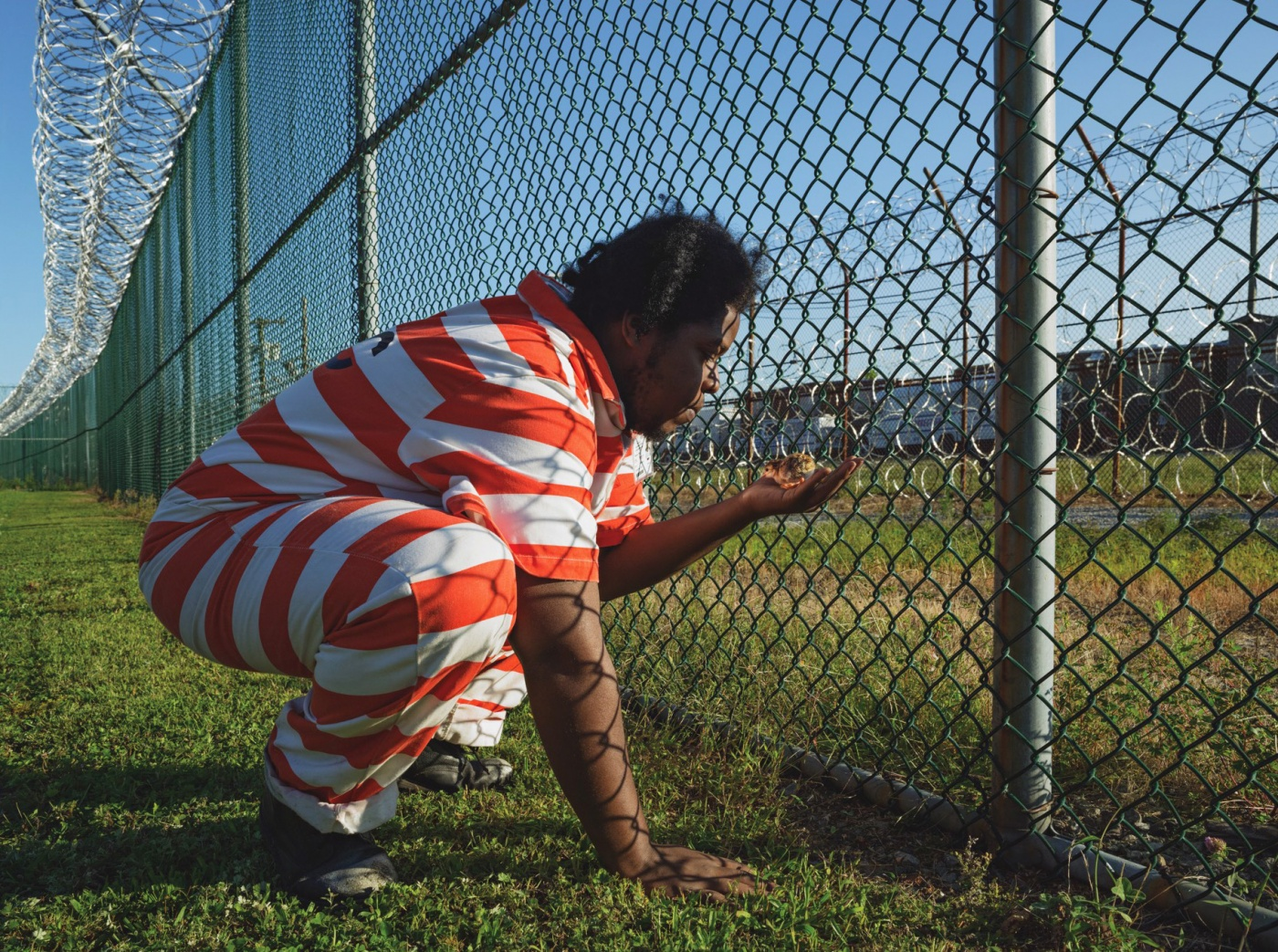 A man wearing a prison uniform squats by a fence, holding a chick in his hand.