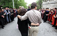 Photo of two people walking at commencement with their arms around each other.