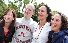 Photo of four people standing, one in a Brown sweatshirt.