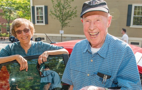 Photo of Bob Traill '43 and Judy Andrews Green '68 in front of a car.